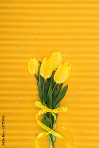 top view of yellow tulip bouquet with ribbon on orange background