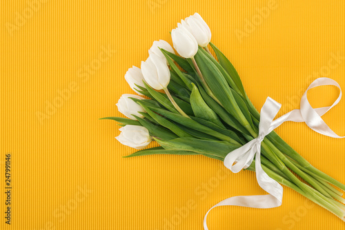 top view of white tulip bouquet with ribbon on orange background
