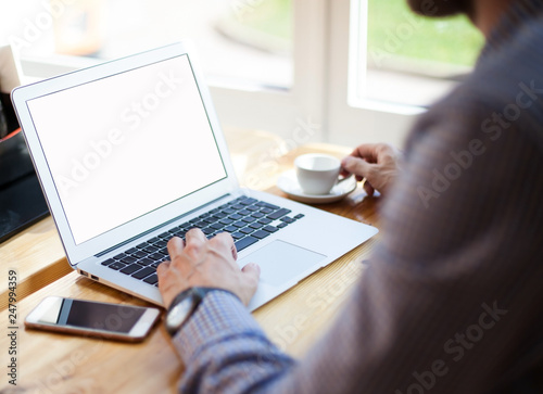 Fototapeta Young businessman sitting in a cafe drinking coffee and working with laptop with blank screen. Business, education, lifestyle concept. Hipster guy working on netbook sitting at coffee shop table. obraz na płótnie