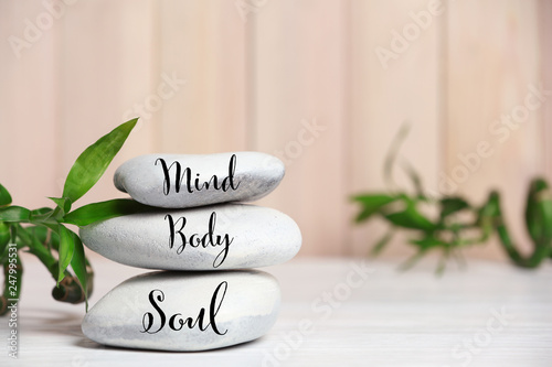 Photo Stands Zen Spa stones and bamboo leaves on table against blurred background. Space for text
