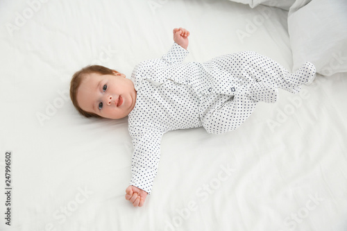 Adorable baby in cute footie on white sheet, above view Tapéta, Fotótapéta