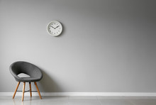 Chair Near White Wall With Clock