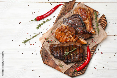Fotografía  Wooden board with different tasty cooked meat and spices on white table