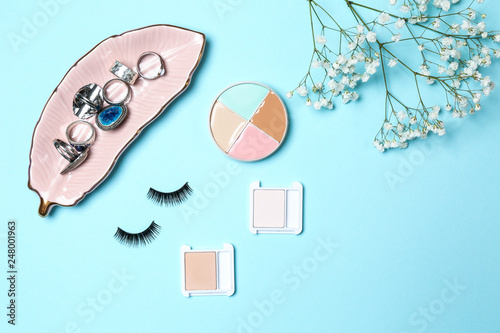 c020e505662 Set of makeup cosmetics with jewelry and false eyelashes on color background