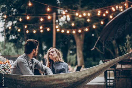 Sensual couple resting on hammock at romantic resort outdoors, summer vacation in the nature concept
