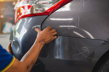 sufferer hand checking of vehicle car bumper dented broken from collision crash damage accident on road,checking cars for scratches and dents