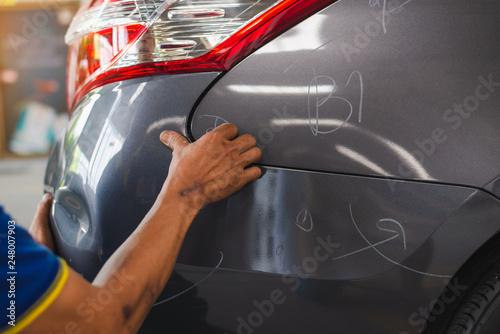 Fototapeta sufferer hand checking of vehicle car bumper dented broken from collision crash