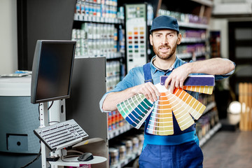 Obraz na SzklePortrait of a handsome workman with color swatches near the equipment for coloring in the building shop