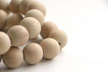 String Of Unvarnished Wooden Beads On A White Surface, Shot With A Short Depth Of Field
