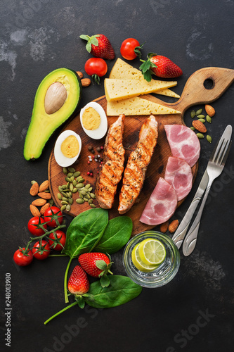 Grilled salmon with boiled egg, ham, vegetables and strawberries on a dark background Canvas Print