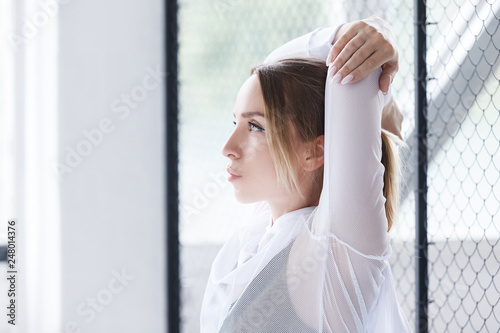 Fotografie, Obraz  Charming young girl pilates instructor doing stretching while standing against the background of the mesh in the gym