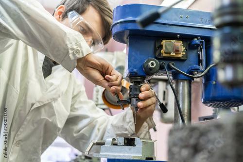 Fotografia  male worker adjust and repair drill machine in the workshop b