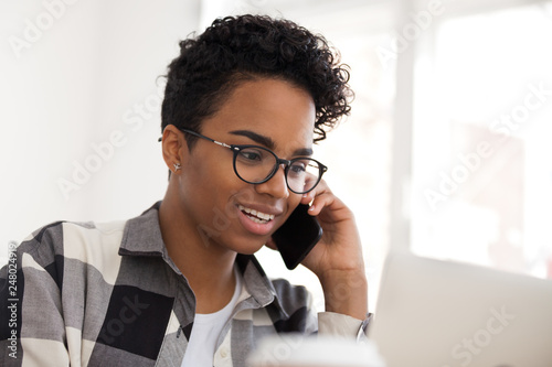 Valokuva  Happy black female saleswoman talking on the phone making call