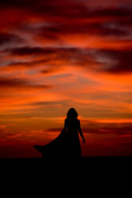 Silhouette Of Young Woman With Long Dress At Sunrise  On The Beach