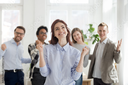Excited employee celebrating business success with happy colleagues at background