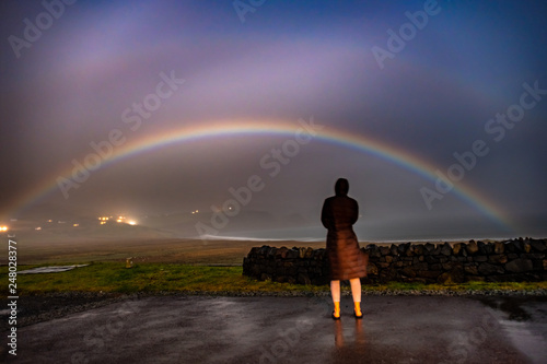Valokuva  Lady observing very rare moonbow during the night above Staffin bay - Isle of Sk