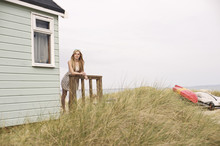 Young Woman Sitting Outside Summer Beach Hut