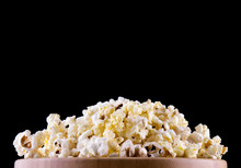 Popcorn In A Wood Cup And On A Wood Table At A Dark Background