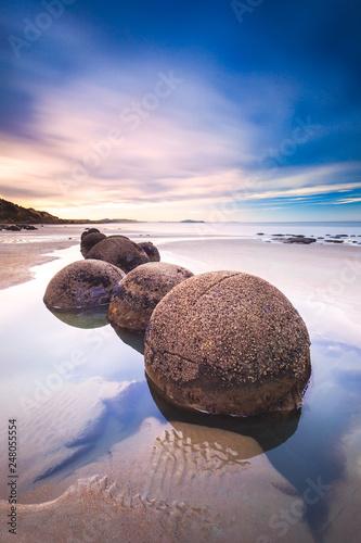 Valokuva  Moeraki boulders in line during beautiful sunset