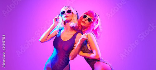 Poster Magasin de musique Fashion. Two DJ girl with Dyed Hair, party makeup in Colorful neon light enjoy music, friends. Disco 80s 90s vibes. Model woman in fashionable bodysuit, make up dancing. Art uv neon banner