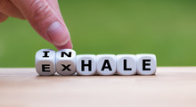 "Inhale,Exhale Concept. Hand Turns Dice And Changes The Word ""INHALE"" To ""EXHALE""."