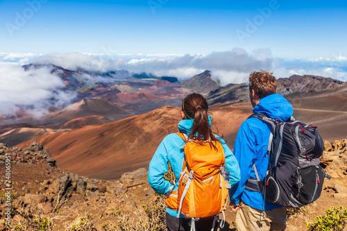 Obraz Hiking people hikers on summit hike at volcano mountain in Maui, Hawaii. Tourists couple trek travel adventure with backpacks. - fototapety do salonu