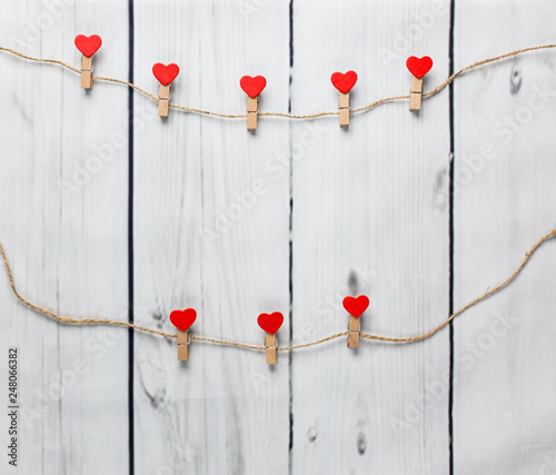 Romantic concept - Clothespins with red hearts on white wooden texture background
