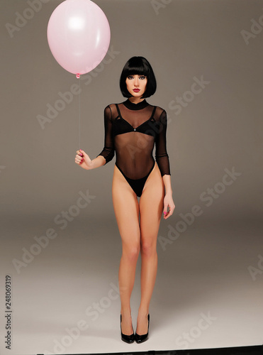Photo The beautiful long-legged girl with a pink balloon poses in studio, she is dress