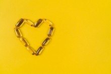 Close Up Capsules Of Fish Fat Oil In The Heart Shape, Omega 3, Vitamin E On The Yellow Background. Healthy Food Diet. Nutritional Supplement