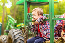 Boy Riding A Tractor On A Farm...