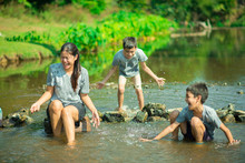 Family Travelling At Waterfall In The Forest Happy Together