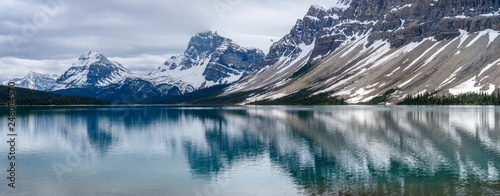 Fotobehang Bergen Bow Lake - A cloudy Spring day panorama of snowcapped peaks, Mt Hector, Bow Peak, BowCrow Peak, Crowfoot Glacier, and Crowfoot Mountain, reflecting in calm and colorful Bow Lake, Banff National Park.