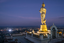 An Iconic Standing Buddha On Wat Phra That Khao Noi One Of The Most Tourist Attraction Places In Nan Province Of Northern Thailand. Night View Of Nan Province.