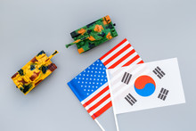 War, Confrontation Concept. Korea, USA. Tanks Toy Near Korean And American Flag On Grey Background Top View