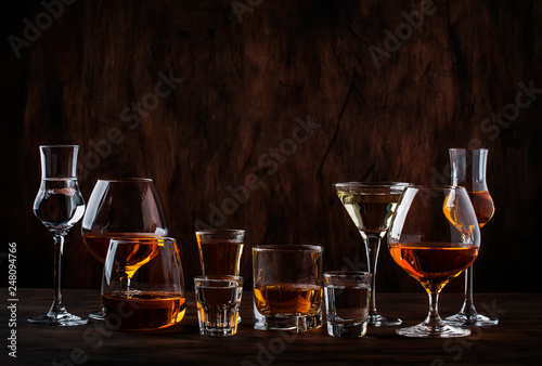 Poster de jardin Bar Selection of hard strong alcoholic drinks in big glasses and small shot glass in assortent: vodka, cognac, tequila, brandy and whiskey, grappa, liqueur, vermouth, tincture, rum.
