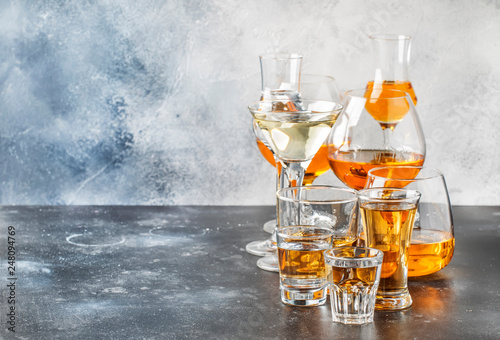 Photo sur Toile Alcool Selection of hard strong alcoholic drinks in big glasses and small shot glass in assortent: vodka, rum, cognac, tequila, brandy and whiskey, grappa, liqueur, vermouth, tincture, rum.