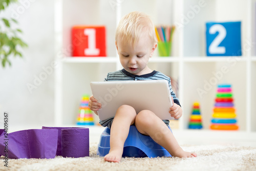 Funny child boy sitting on chamber pot with tablet computer Wallpaper Mural