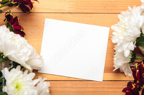Foto  Frame of white and red chrysanthemum flowers on craft paper