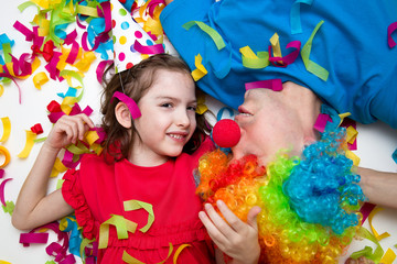 Holiday. Girl 6 years old in red dress with cap  and the man in the clown wig is having fun. Background colored confetti.