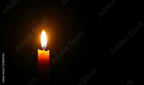Fototapeta Yellow candle light burn against black background