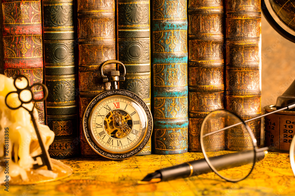 Fototapeta Antique clock on the background of vintage books. Mechanical clockwork on a chain. Fountain pen and glasses.