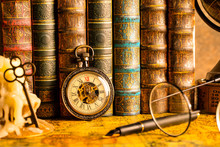 Antique Clock On The Background Of Vintage Books. Mechanical Clockwork On A Chain. Fountain Pen And Glasses.