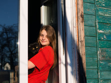 Girl With A Cat Waiting For Spring At The Window