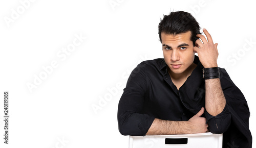 Fotografija  dark-haired young man sitting on a chair on an isolated background