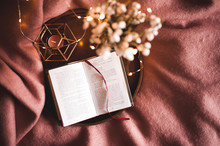 Open Book With Candle And Fresh Flowers On Wooden Tray In Room. Spring Season.