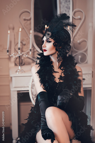 Fotografía elegant woman in retro style of the 20s, lady flapper in a black dress, dark hair and a bandage, feather boa, long gloves
