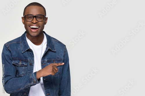 Fotografia  Happy excited african man laughing pointing finger at copy space