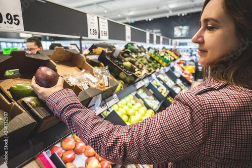 Plakat Kobieta w supermarkecie robi zakupy wybiera avocados pokazuje jej konsumeryzm na rynku z tłem i zamazującymi ocenami. Dziewczyna patrząc na produkty, pu