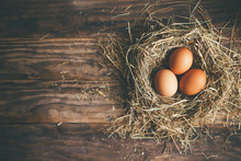 Fresh Chicken Eggs In The Nest On A Rustic Background