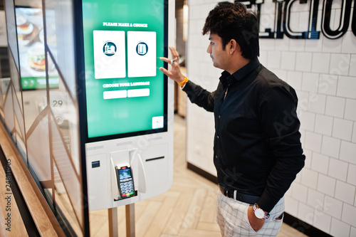 Indian man customer at store place orders and pay through self pay floor kiosk for fast food, payment terminal Wallpaper Mural